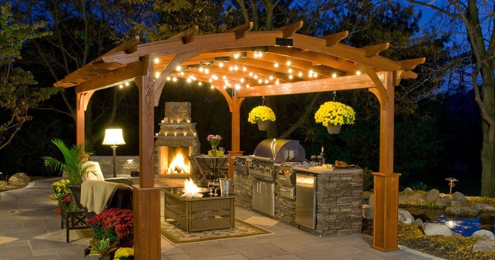 Пергола освещенная фонариками, под которой находится камин, барбекю, садовые кресла и столик